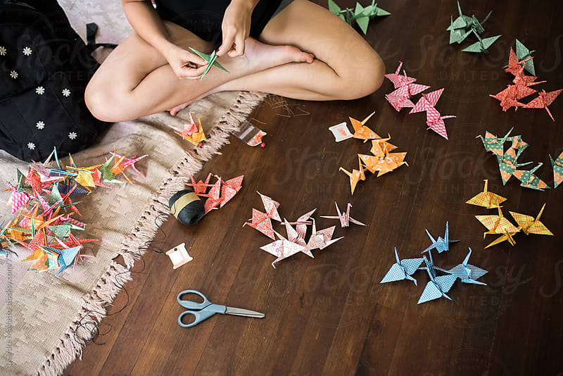making an origami crane chain by Deirdre Malfatto for Stocksy United