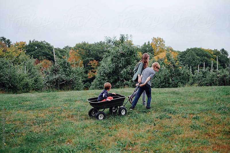 kids pulling  wagon with little brother in it by Léa Jones for Stocksy United