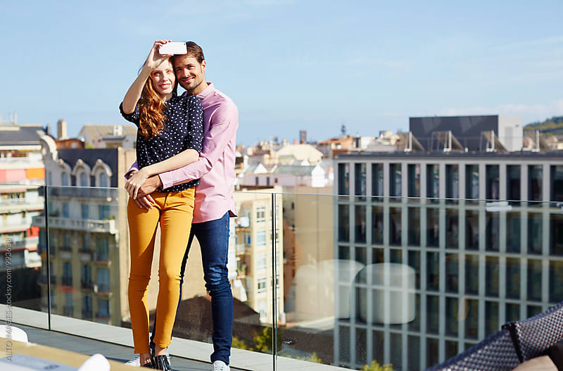 Happy Couple Taking Selfie On Hotel Terrace by ALTO IMAGES for Stocksy United