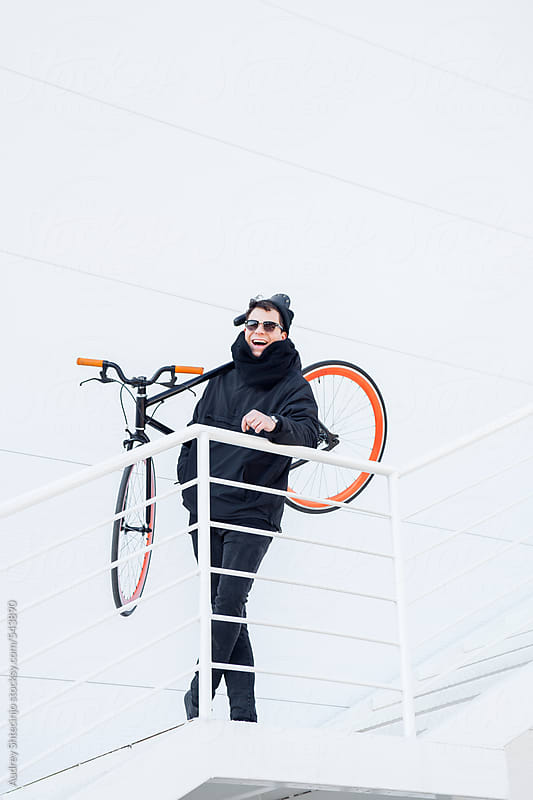 Handsome male in black outfit with his bicycle in white space. by Audrey Shtecinjo for Stocksy United