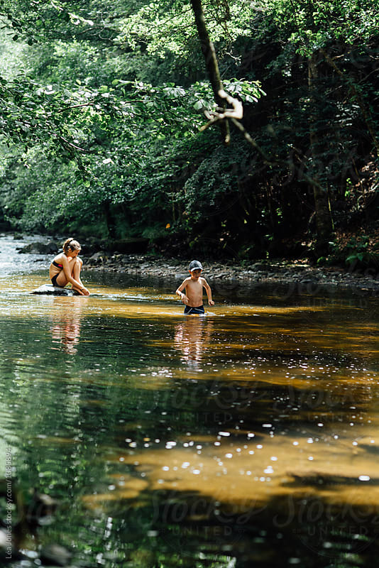 children playing in a river by Léa Jones for Stocksy United