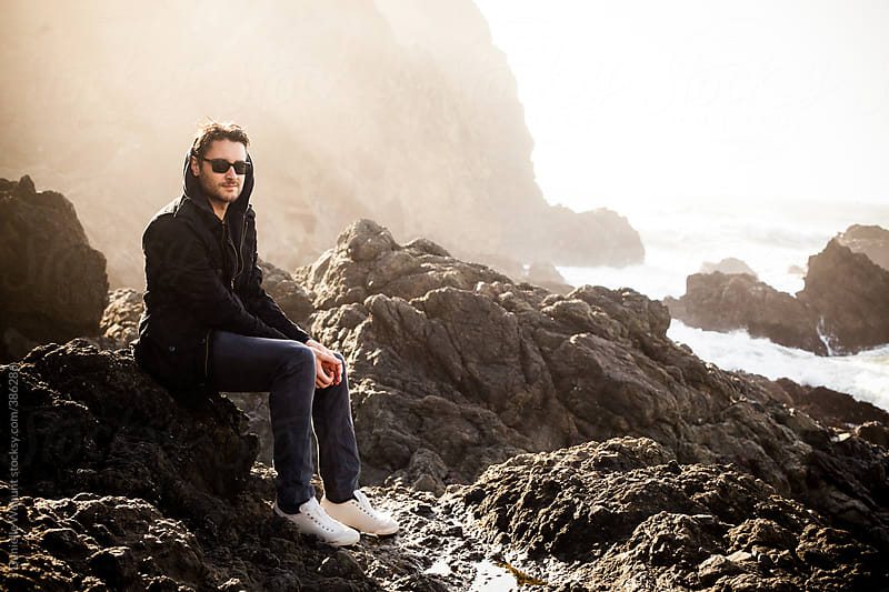 Man with sunglasses in black jacket sitting on rocks by the ocean shore by J Danielle Wehunt for Stocksy United