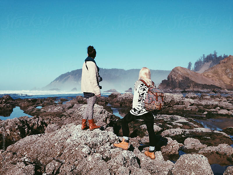 Two Girls Stand On Coastal Rocks by Kevin Gilgan for Stocksy United