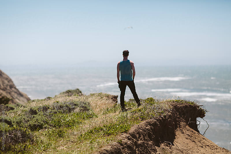 Strong brunette man stands overlooking the pacific ocean on a cliff by HOWL for Stocksy United
