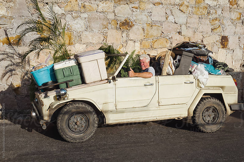 Senior man using overloaded old safari car as moving truck by Per Swantesson for Stocksy United