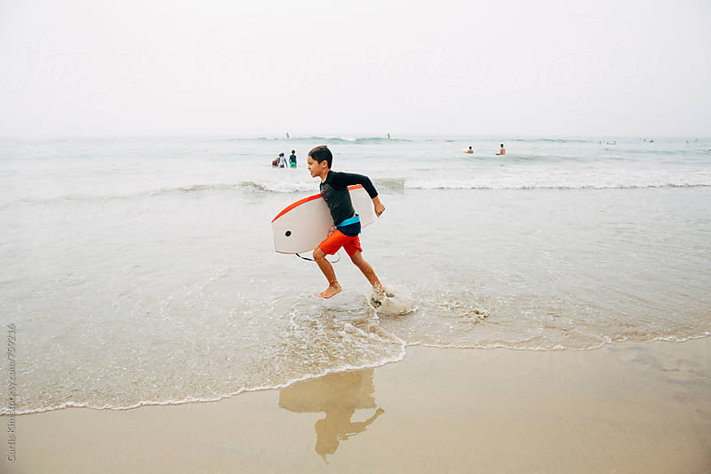 Boy running on the beach with his boogie board by Curtis Kim for Stocksy United