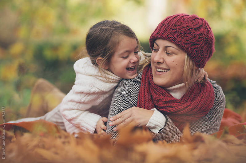 Mother and daunter laughing in the park by Dejan Ristovski for Stocksy United