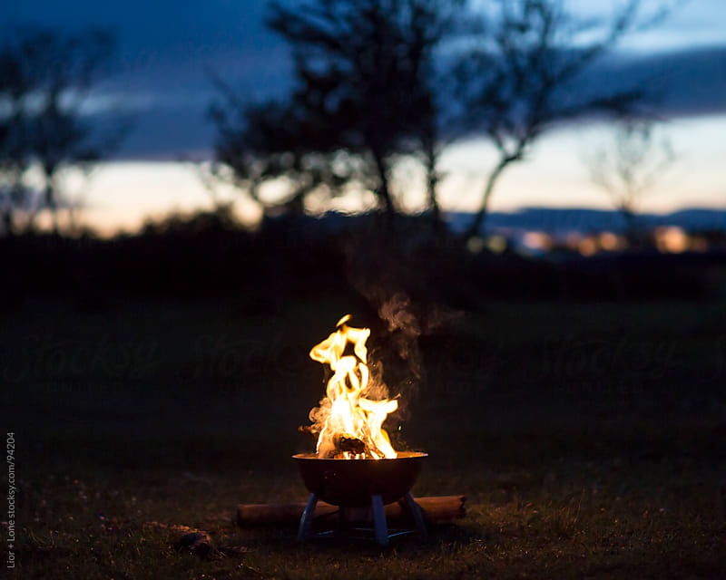Small wood fire in a field at dusk by Lior + Lone for Stocksy United