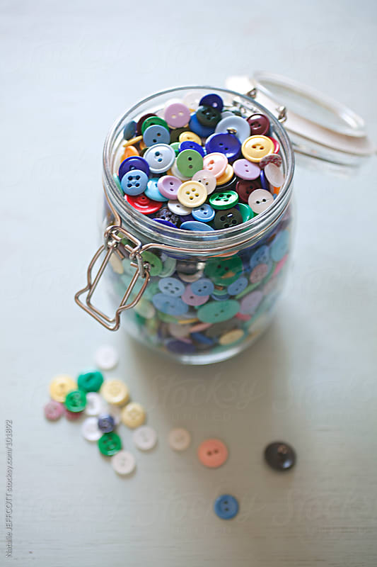 open jar on table overflowing with colourful buttons by Natalie JEFFCOTT for Stocksy United