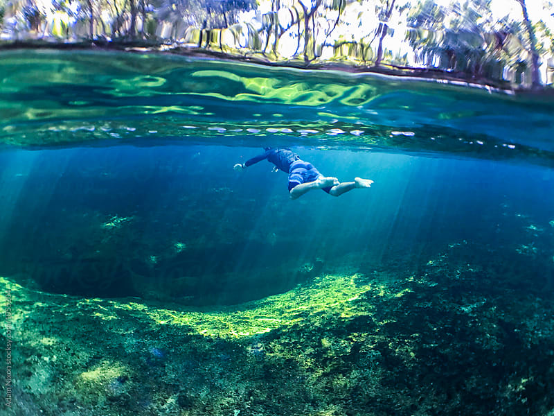 A teenager snorkeling in a fresh water spring in Florida by Adam Nixon for Stocksy United