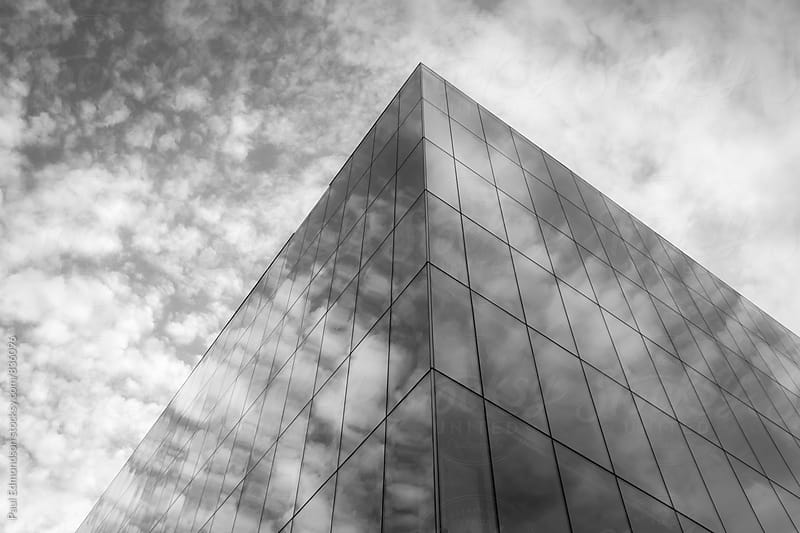 Low angle view of modern office building and sky, clouds reflecting in windows by Paul Edmondson for Stocksy United