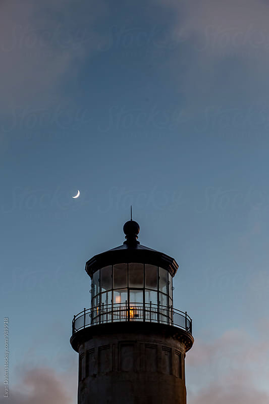 Lighthouse at Dust with Crescent Moon by Evan Dalen for Stocksy United