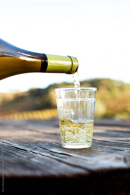 White Wine Being Poured Into Small Glass On Picnic Table by Sara Remington for Stocksy United