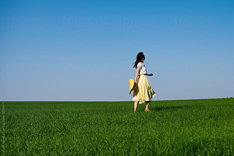 Back view of brunette with sunhat in field by Danil Nevsky for Stocksy United