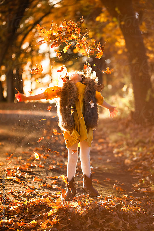 A girl jumps into the air while throwing leaves up, autumn by Amanda Worrall for Stocksy United