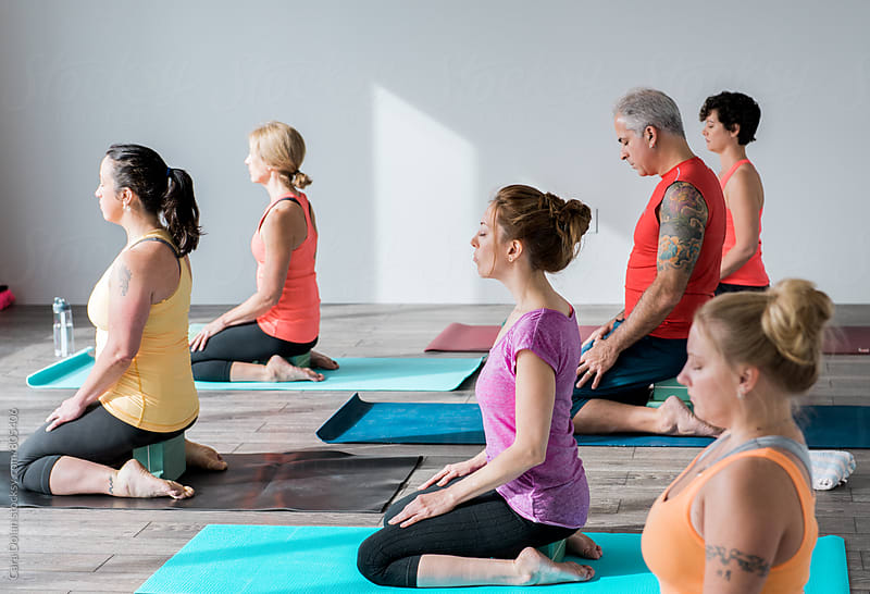 Yoga class in modern studio by Cara Slifka for Stocksy United