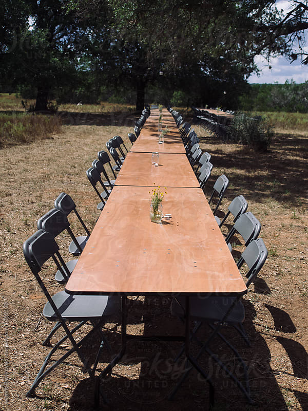 Long dining table set up for outdoor wedding reception by Jeremy Pawlowski for Stocksy United