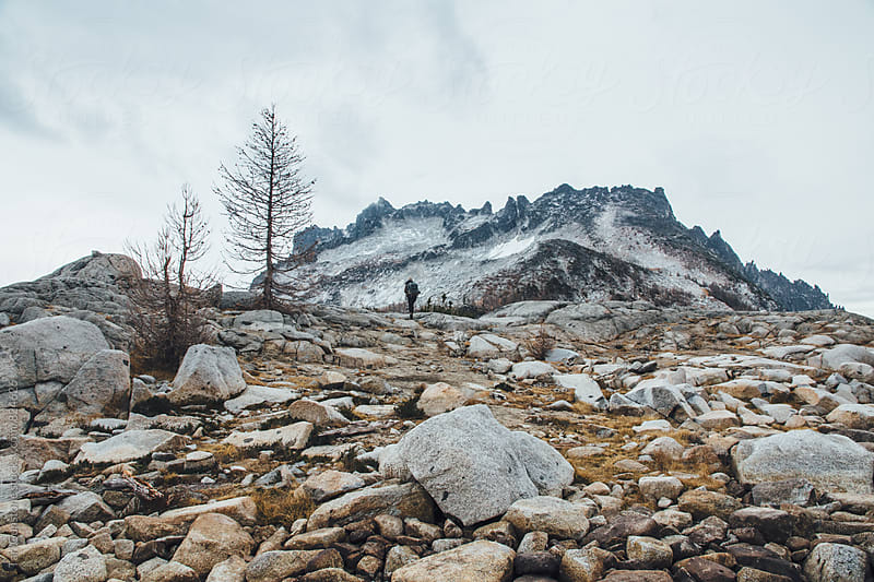 Rocky wild landscape with hiker in distance by Tari Gunstone for Stocksy United
