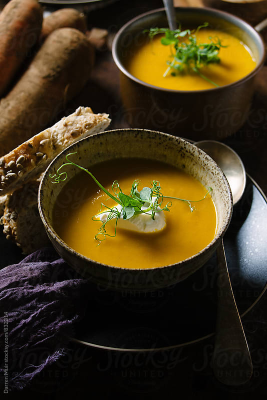 A serving of carrot soup with sour cream and pea shoots in a rustic setting. by Darren Muir for Stocksy United