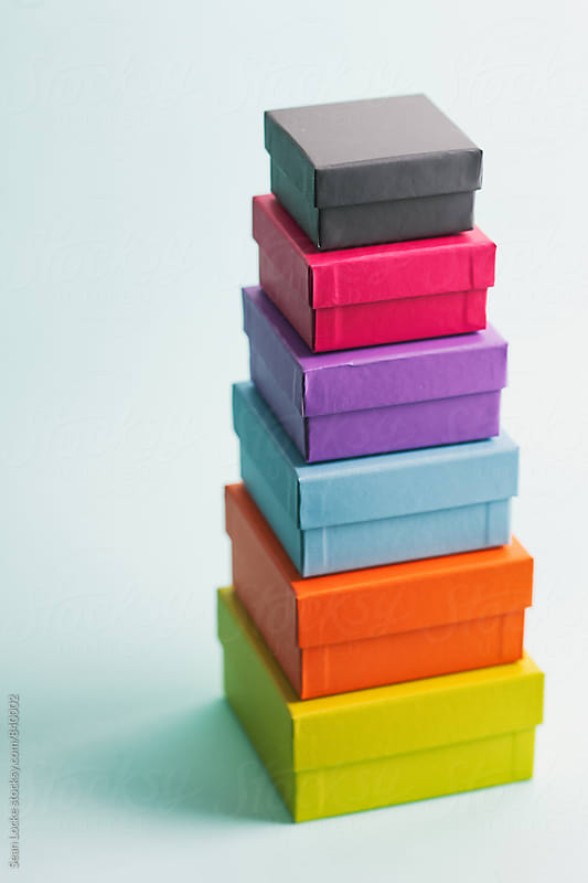 Tiny Colored Boxes Stacked Against Blue by Sean Locke for Stocksy United