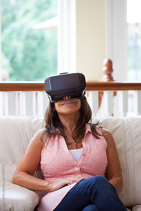 VR: Mature Woman Sits Back To Enjoy Virtual Reality Headset by Sean Locke for Stocksy United