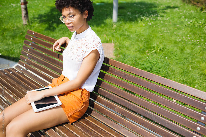 Young woman relaxing on the bench in a park by michela ravasio for Stocksy United
