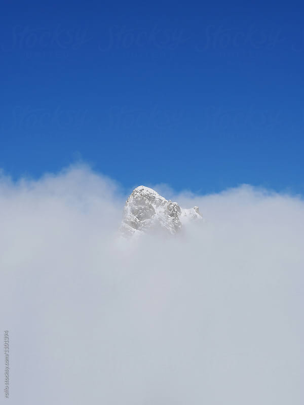 Mountain peak in clouds under bright blue sky by rolfo for Stocksy United