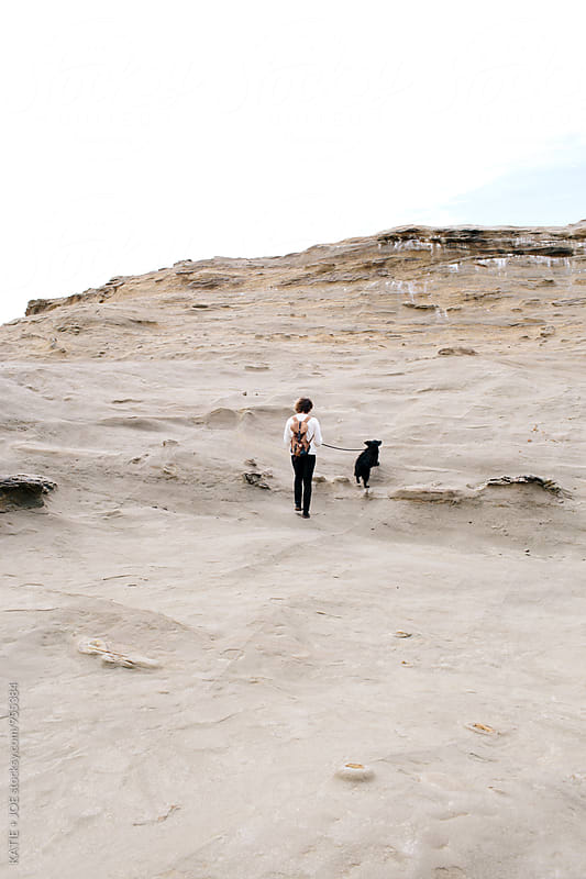 Man and dog walking up a sandy rocky hill by KATIE + JOE for Stocksy United