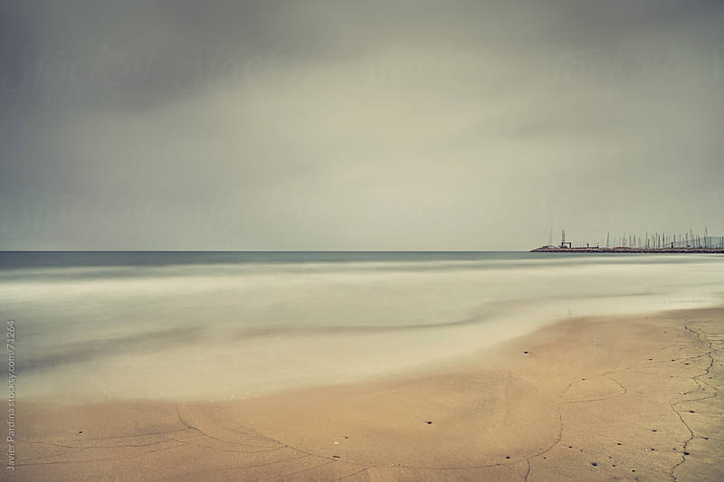 Cloudy day at the beach with long exposure by Javier Pardina for Stocksy United