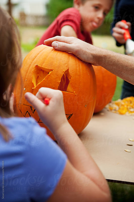Pumpkins: Little Girl Carving Face on Pumpkin by Sean Locke for Stocksy United