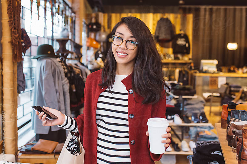 Smiling woman shopping in local urban store by Carey Shaw for Stocksy United