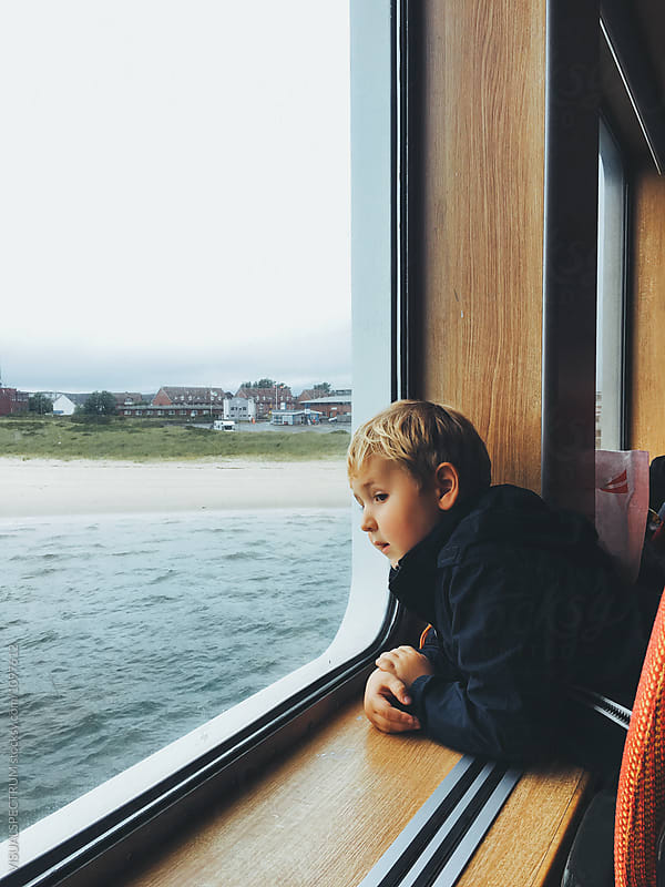 Blond Caucasian Boy Looking Out Window on North Sea Ferry (Sylt, Germany) by Julien L. Balmer for Stocksy United