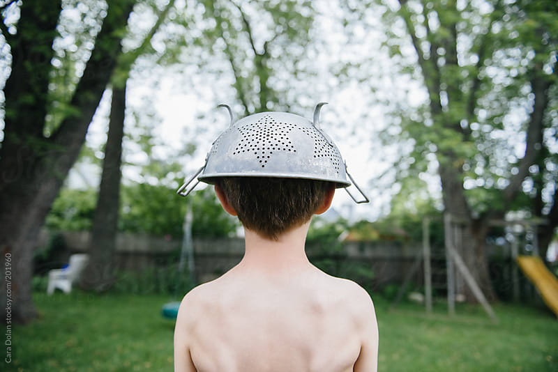 Boy wearing colander on his head looks out into his backyard by Cara Dolan for Stocksy United