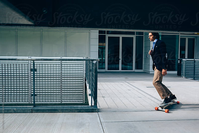 Young businessman going to work on a skateboard by michela ravasio for Stocksy United