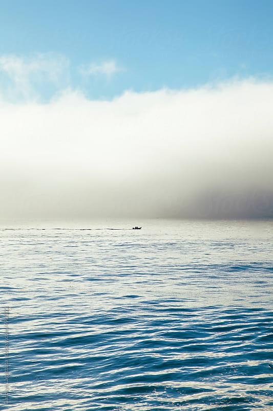 Singular fishing boat in the ocean on a foggy morning by Carolyn Lagattuta for Stocksy United