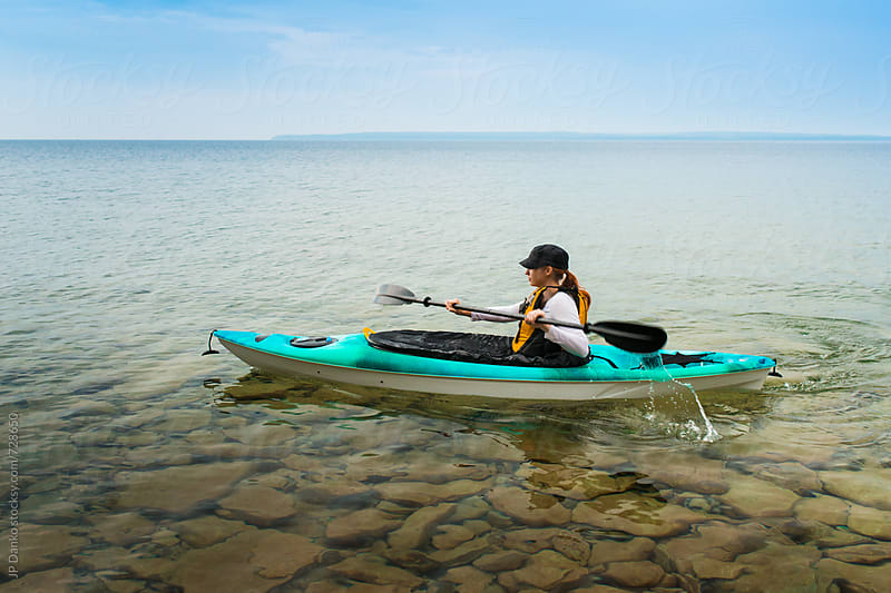 Woman Paddling Sea Kayak on Crystal Clear Freshwater Lake at Summer Family Cottage by JP Danko for Stocksy United