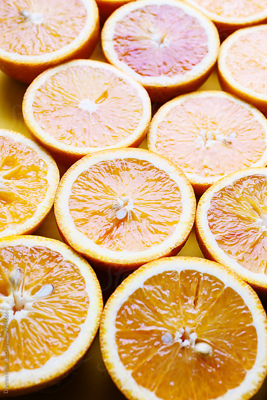 Oranges on a yellow background.Half oranges. by Darren Muir for Stocksy United