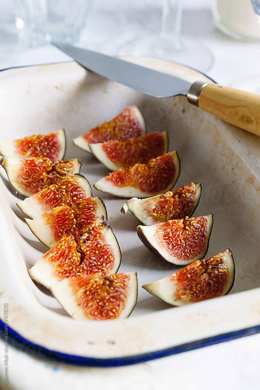 A  tray of sliced ripe figs, ready to garnish a dessert. by Darren Muir for Stocksy United