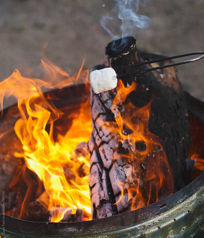 A marshmallow roasts over an open campfire by Tana Teel for Stocksy United