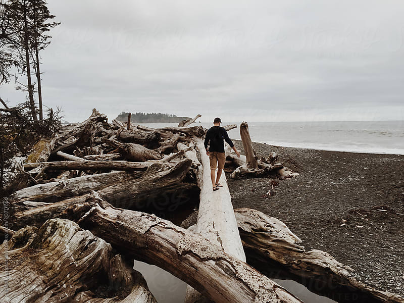 Man Hiking/Walking on a Driftwood Trunk on the Shore of the Pacific Ocean by michelle edmonds for Stocksy United