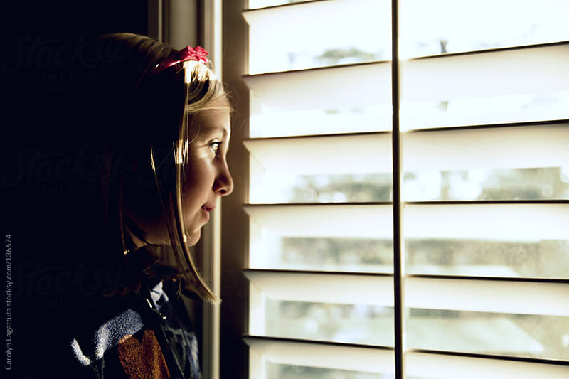 Young girl looking out the window, anxious for her friends to arrive by Carolyn Lagattuta for Stocksy United