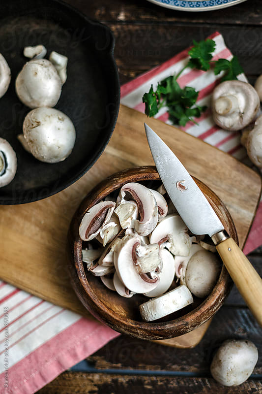 Sliced mushrooms in a wooden bowl on a cutting board. by Darren Muir for Stocksy United