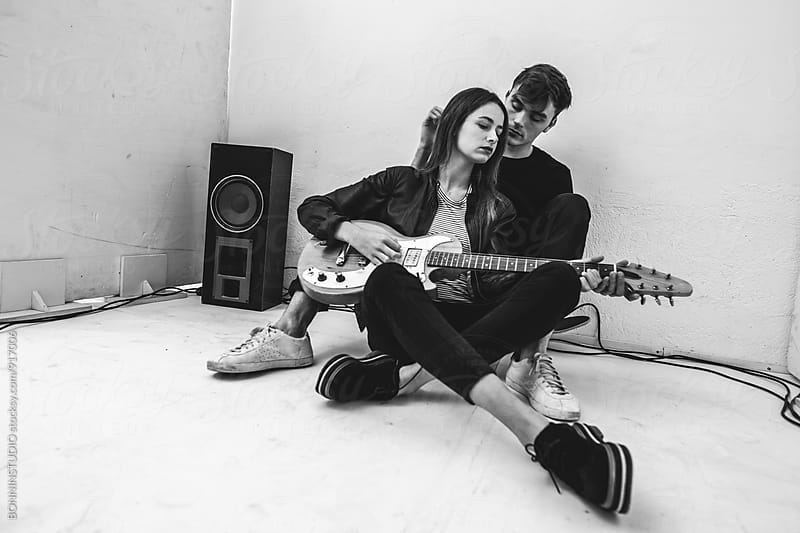 Rockers couple composing with electric guitar in recording studio. by BONNINSTUDIO for Stocksy United