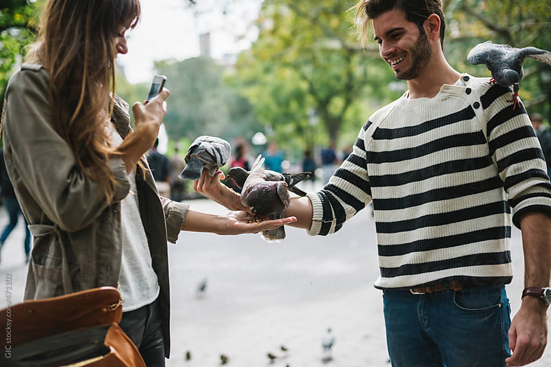 Friends taking pictures with pigeons in the city by GIC for Stocksy United