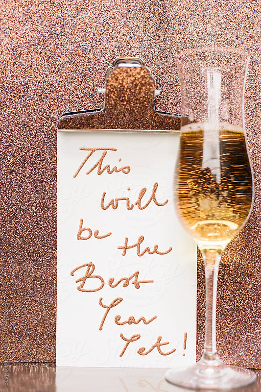New year message with a glass of champagne in front of a glitter background by Beatrix Boros for Stocksy United