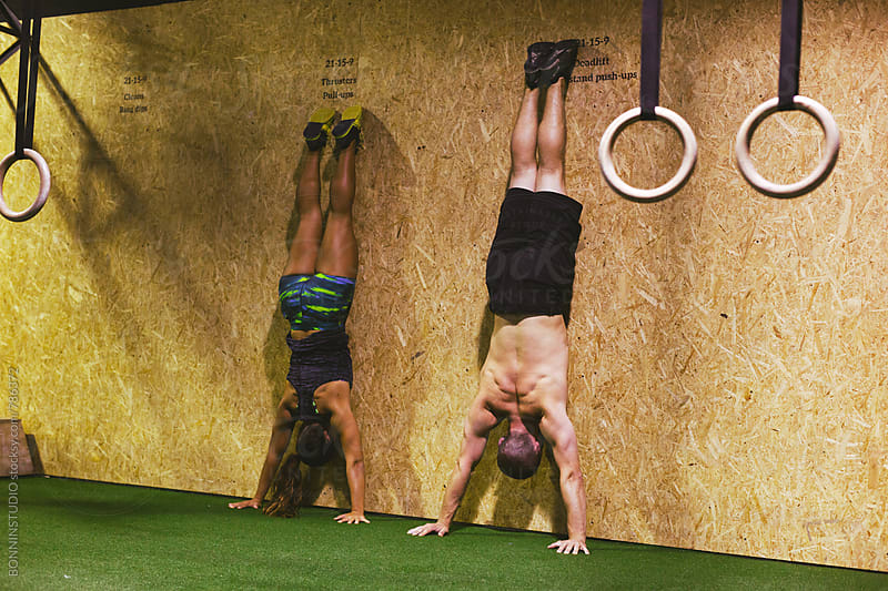 Couple doing a handstand at gym. by BONNINSTUDIO for Stocksy United