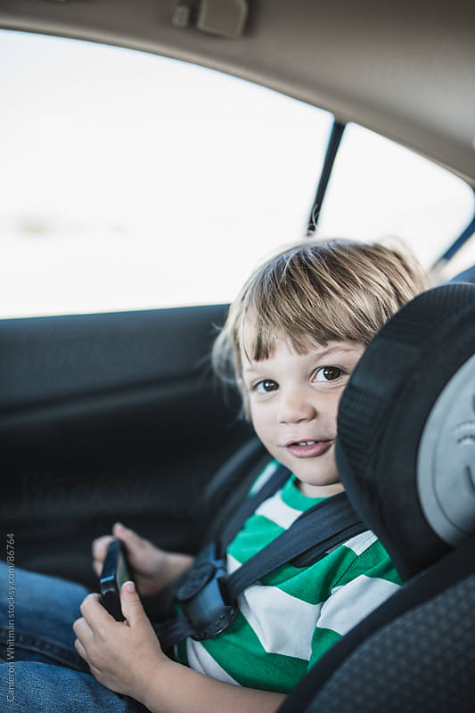 Little Boy Playing Games In Car Seat  by Cameron Whitman for Stocksy United