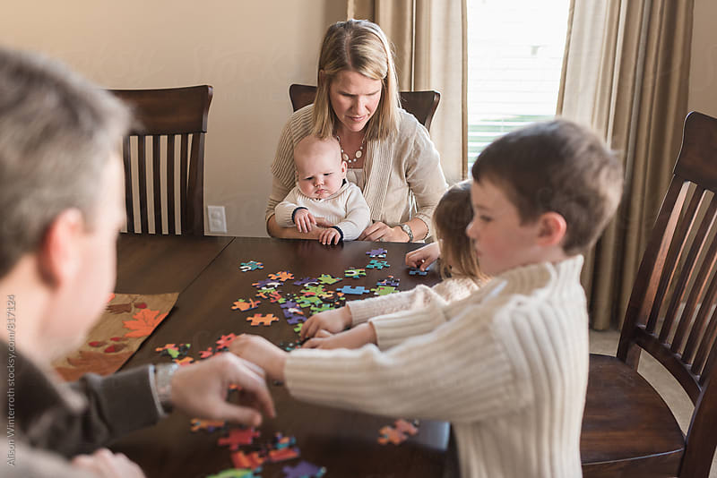 A Large Family Plays With A Puzzle by Alison Winterroth for Stocksy United