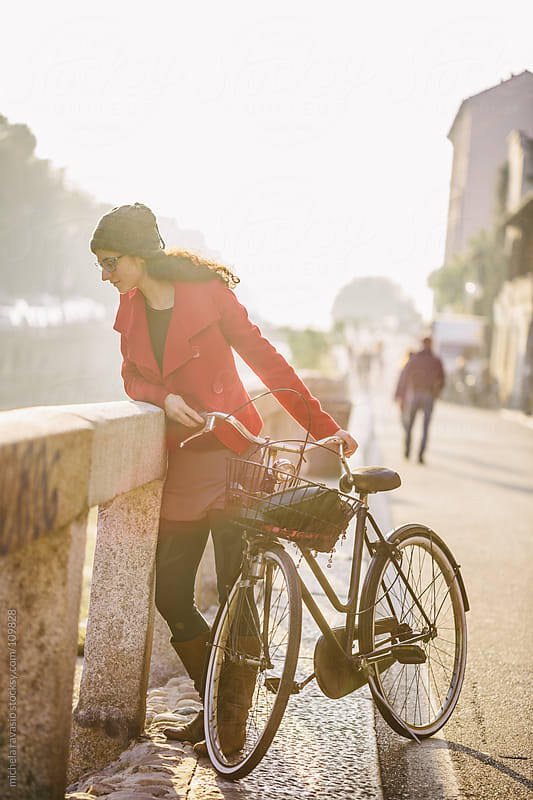 Young woman with a bicycle looking at the canal in Milan by michela ravasio for Stocksy United
