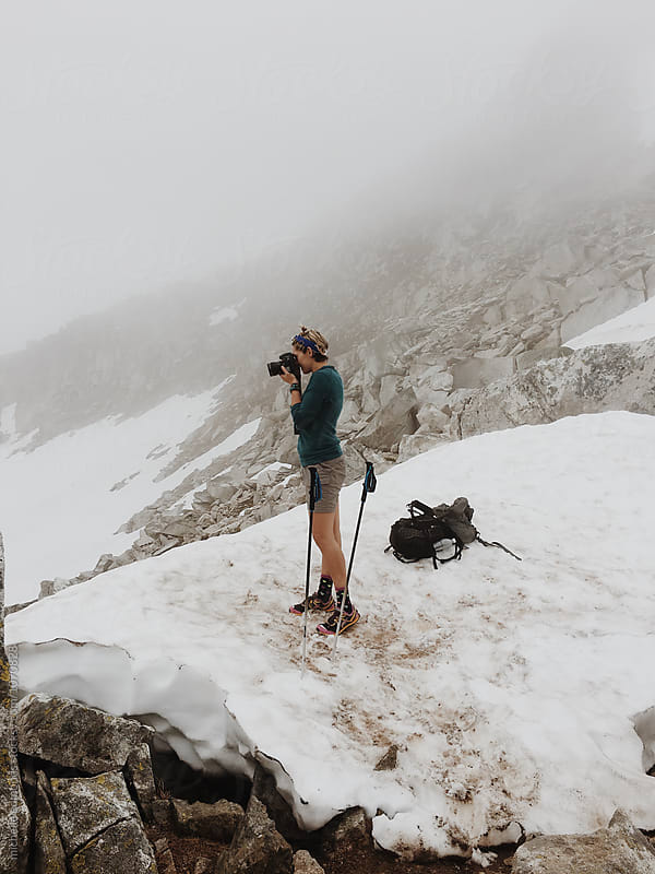 Female Photographer Taking a Photo on a Mountain Peak in Snow by michelle edmonds for Stocksy United
